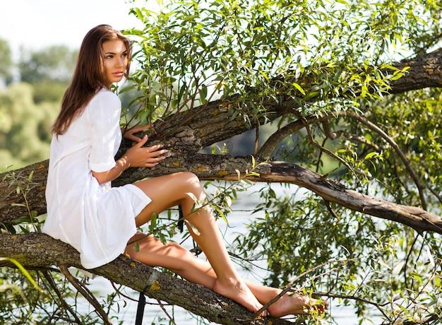 Giovane donna castana in vestito bianco che si siede sul tronco di albero sopra l'acqua il giorno di estate con la natura verde al fondo Foto Premium