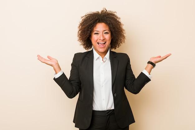 La giovane donna afroamericana di affari fa la scala con le armi, si sente felice e sicura. Foto Premium