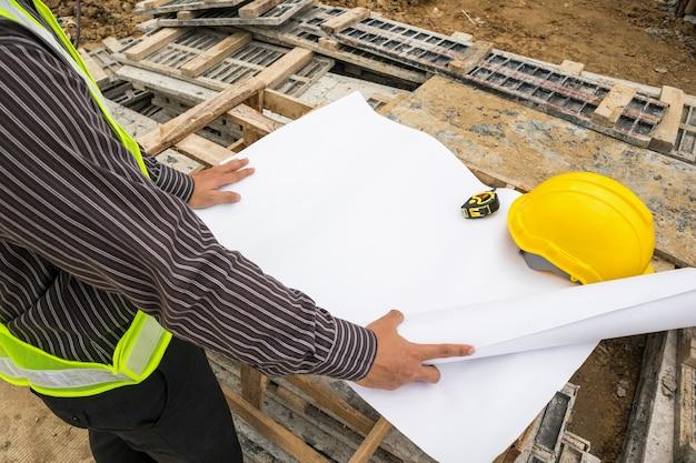 Lavoratore di ingegnere professionista giovane uomo d'affari presso il cantiere edile casa con progetto Foto Premium