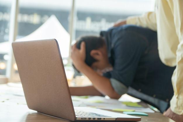Un giovane uomo d'affari tiene la testa in testa a causa della delusione. Foto Premium