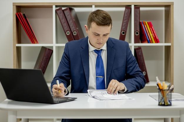 Giovane uomo d'affari che lavora con i documenti guardando attraverso i documenti nella cartella, seduto alla scrivania in ufficio. Foto Premium