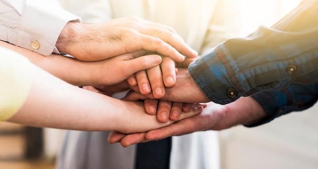 Giovani persone di affari che uniscono le loro mani Foto Premium