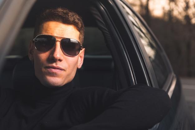 Giovane adulto caucasico all'interno di un'auto sportiva Foto Premium