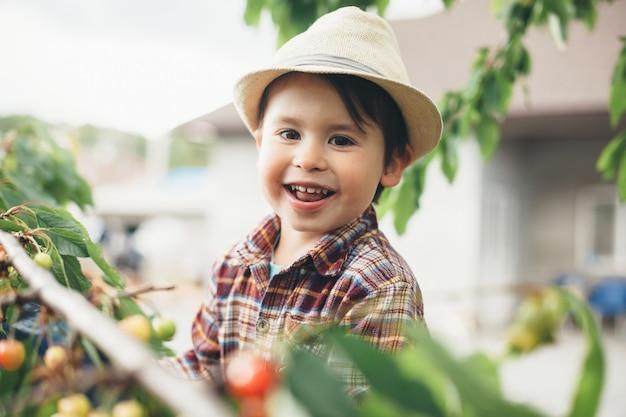 Giovane ragazzo caucasico che guarda l'obbiettivo mentre era seduto nella struttura ad albero e mangiare le ciliegie Foto Premium