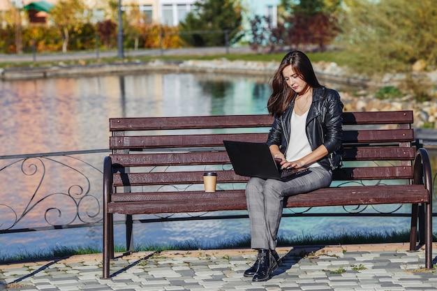 Giovane donna caucasica di affari che si siede alla panchina nel parco e lavora con il computer portatile Foto Premium
