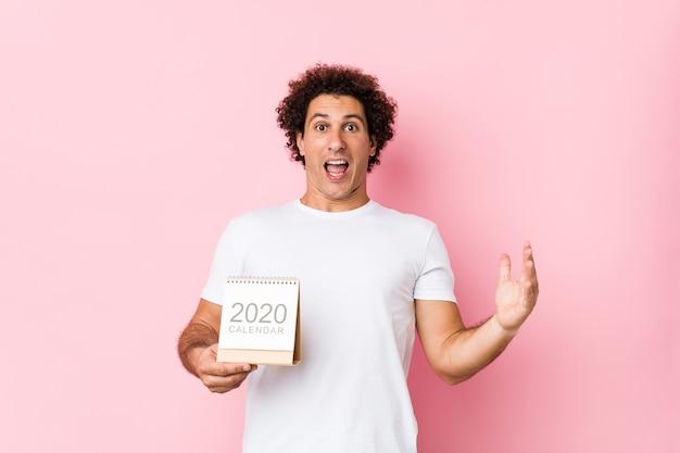 Giovane uomo riccio caucasico che tiene un calendario 2020 che celebra una vittoria o un successo Foto Premium