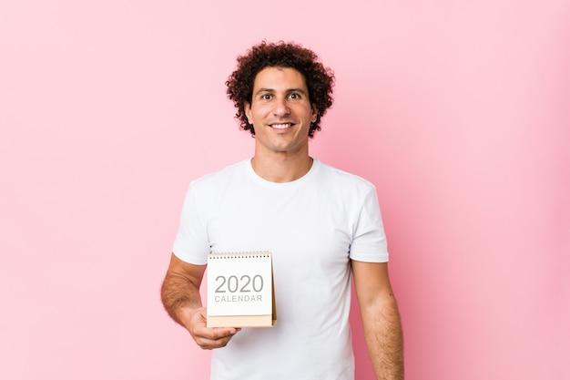 Giovane uomo riccio caucasico che giudica un calendario 2020 felice, sorridente e allegro. Foto Premium