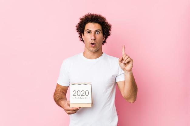 Giovane uomo riccio caucasico che tiene un calendario 2020 che ha una grande idea, concetto di creatività. Foto Premium