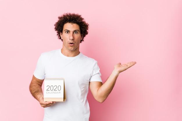 Il giovane uomo riccio caucasico che tiene un calendario 2020 ha colpito lo spazio della copia della tenuta sulla palma. Foto Premium