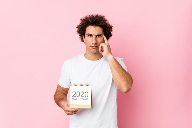 Giovane uomo riccio caucasico che tiene un calendario 2020 che indica il suo tempio con il dito, pensando, concentrato su un compito. Foto Premium
