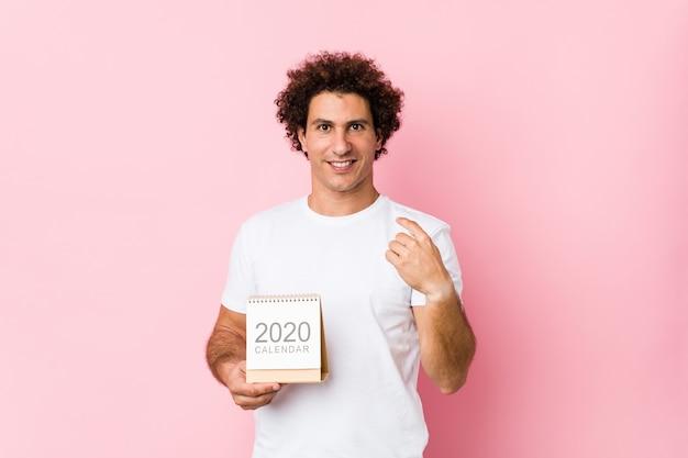 Giovane uomo riccio caucasico che tiene un calendario 2020 che indica con il dito come se l'invito si avvicini. Foto Premium