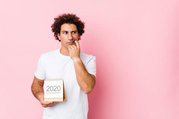 Il giovane uomo riccio caucasico che tiene un calendario 2020 si è disteso pensando a qualcosa che esamina uno spazio della copia. Foto Premium