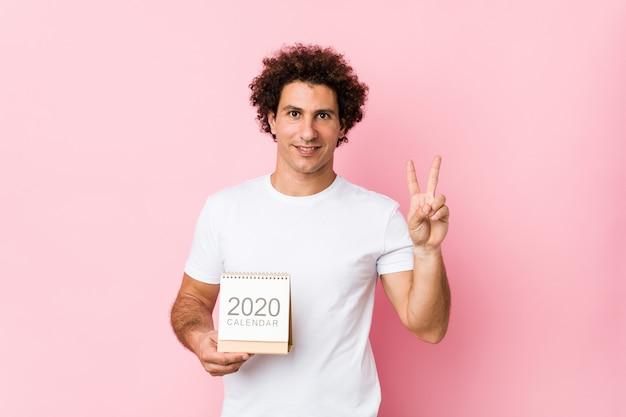 Giovane uomo riccio caucasico che tiene un calendario 2020 che mostra numero due con le dita. Foto Premium