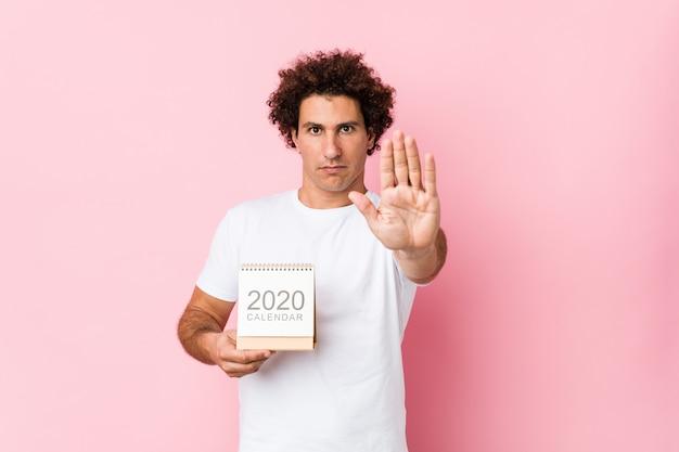 Giovane uomo riccio caucasico che tiene un calendario 2020 che sta con la mano tesa che mostra il fanale di arresto, impedente. Foto Premium