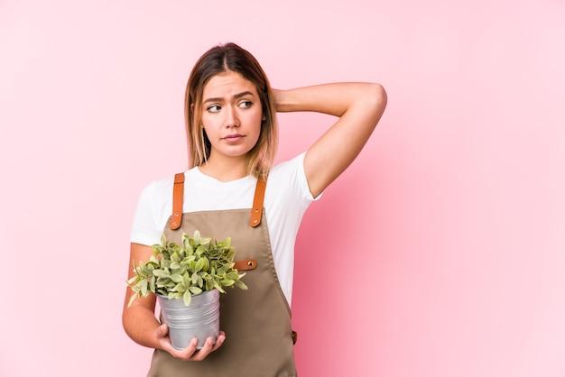 Giovane donna caucasica giardiniere sul rosa toccando la parte posteriore della testa, pensando e facendo una scelta. Foto Premium