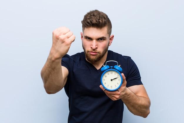 Giovane uomo caucasico che tiene sveglia che mostra pugno, espressione facciale aggressiva. Foto Premium