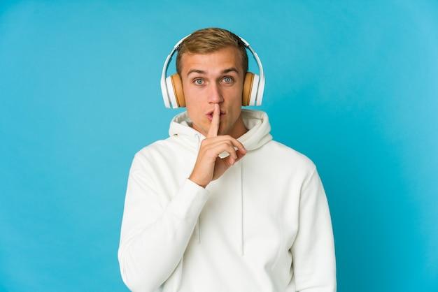 Musica d'ascolto del giovane uomo caucasico isolata sull'azzurro che mantiene un segreto o che chiede il silenzio. Foto Premium
