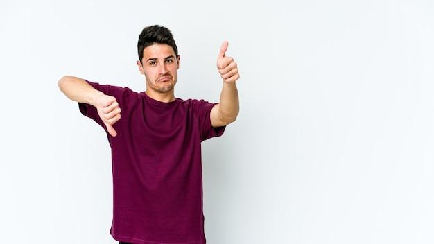 Giovane uomo caucasico che mostra i pollici in su e in giù, difficile scegliere il concetto Foto Premium