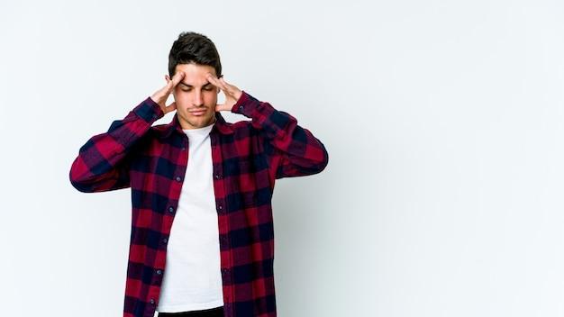 Giovane uomo caucasico toccando le tempie e avendo mal di testa. Foto Premium