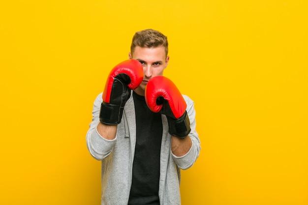 Giovane uomo caucasico che indossa guantoni da boxe Foto Premium