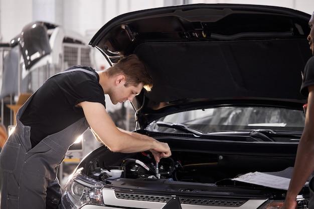Giovane meccanico professionista caucasico in un servizio di auto Foto Premium