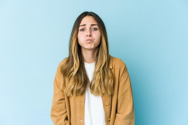 La giovane donna caucasica soffia sulle guance, ha un'espressione stanca. concetto di espressione facciale. Foto Premium