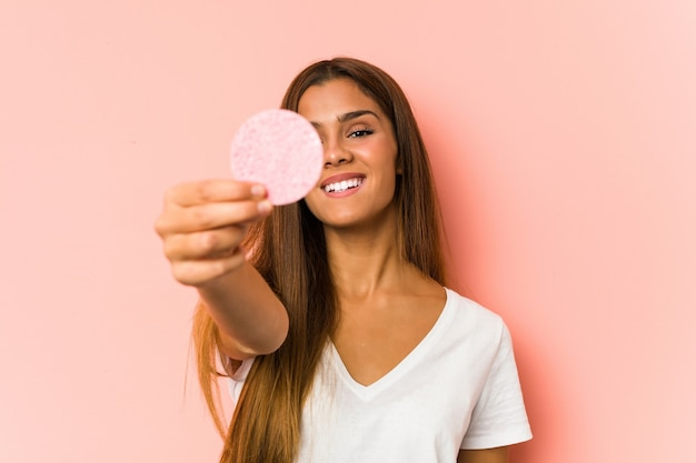 Giovane donna caucasica che pulisce il suo fronte con un disco facciale isolato Foto Premium
