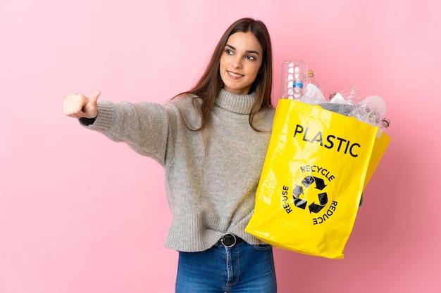 Giovane donna caucasica che tiene un sacchetto pieno di bottiglie di plastica da riciclare isolato su rosa dando un pollice in alto gesto Foto Premium