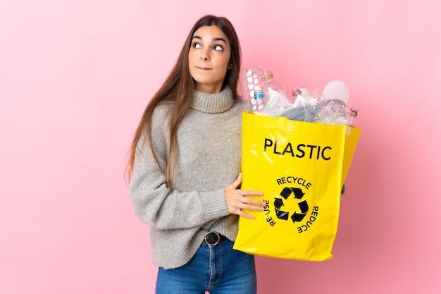 Giovane donna caucasica che tiene un sacchetto pieno di bottiglie di plastica da riciclare isolato sul rosa avendo dubbi e pensando Foto Premium
