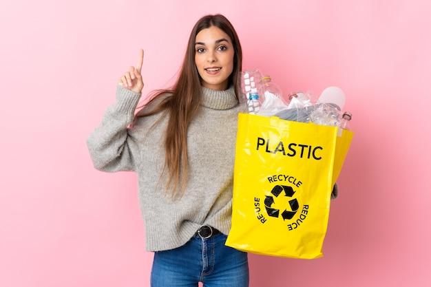 Giovane donna caucasica che tiene un sacchetto pieno di bottiglie di plastica da riciclare isolato sul rosa rivolto verso l'alto una grande idea Foto Premium