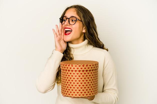 La giovane donna caucasica che tiene una casella di giorno di biglietti di s. valentino del cuore ha isolato gridando e tenendo il palmo vicino alla bocca aperta. Foto Premium