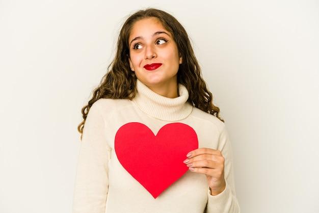 La giovane donna caucasica che tiene una forma di giorno di biglietti di s. valentino del cuore ha isolato il sogno di raggiungere obiettivi e scopi Foto Premium