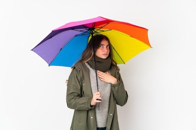 Giovane donna caucasica che tiene un ombrello isolato su priorità bassa bianca che ha dubbi e pensiero Foto Premium