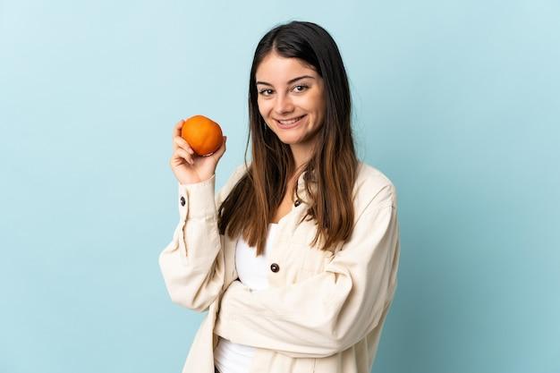Giovane donna caucasica isolata sull'azzurro che tiene un'arancia Foto Premium