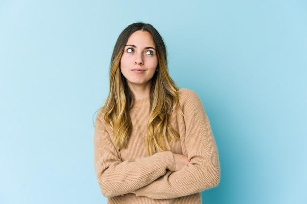 Giovane donna caucasica isolata sulla parete blu che sogna di raggiungere obiettivi e scopi Foto Premium