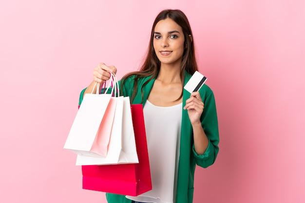 Giovane donna caucasica isolata sui sacchetti della spesa rosa della tenuta e una carta di credito Foto Premium