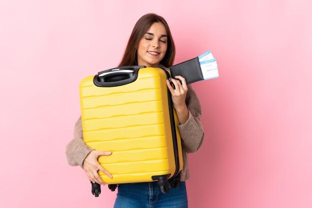 Giovane donna caucasica isolata sul rosa in vacanza con la valigia e il passaporto Foto Premium