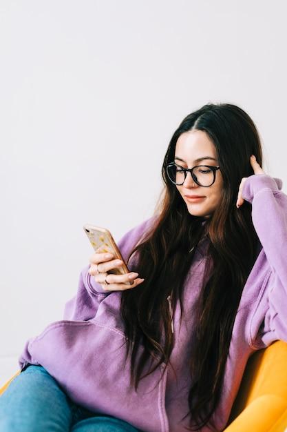 Giovane donna caucasica utilizzando il telefono cellulare, seduto sulla poltrona nel soggiorno. Foto Premium