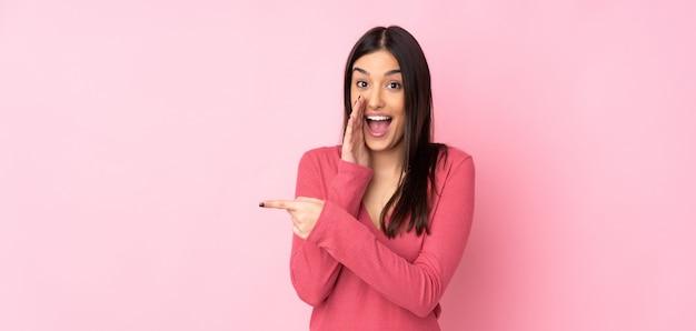 Giovane donna caucasica sul muro che punta verso il lato per presentare un prodotto e sussurrando qualcosa Foto Premium