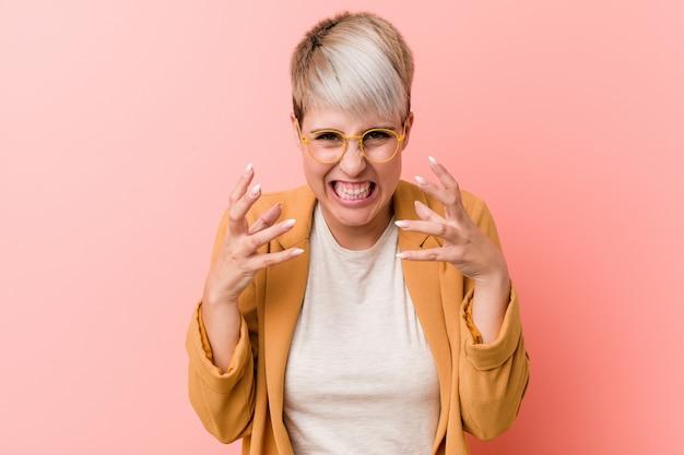 Giovane donna caucasica che indossa un abbigliamento casual business sconvolto urlando con le mani tese. Foto Premium