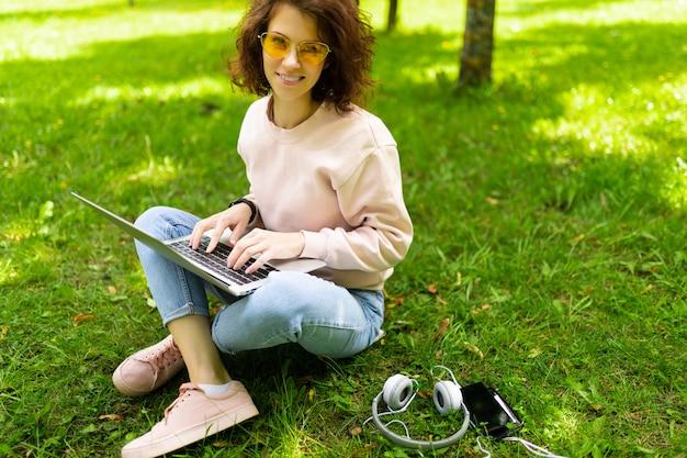 La giovane donna caucasica con il sorriso perfetto, le labbra carnose, gli occhiali cammina nella natura, si siede su un'erba con il computer portatile e comunica con gli amici o lavora Foto Premium