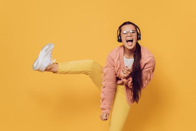 Giovane bruna allegra con gli occhiali che balla, ascolto musica in cuffia sollevando la gamba vestita in pantaloni gialli, scarpe bianche, maglione rosa e cuffie in testa Foto Premium