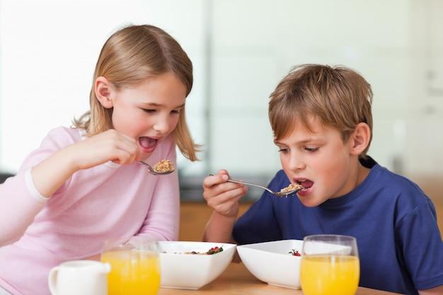 Bambini piccoli facendo colazione Foto Premium