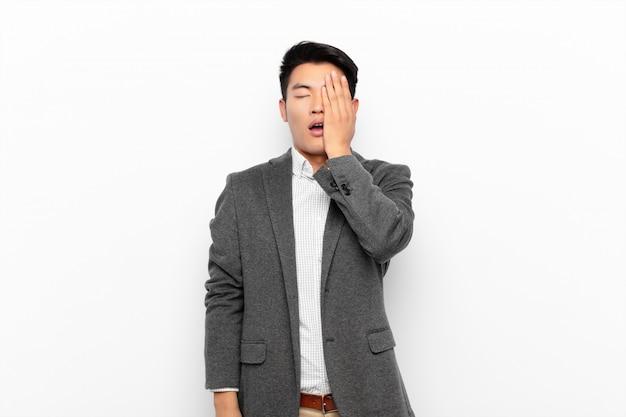 Giovane cinese che sembra assonnato, annoiato e sbadigliando, con un mal di testa e una mano che copre metà del viso contro la parete di colore piatto Foto Premium