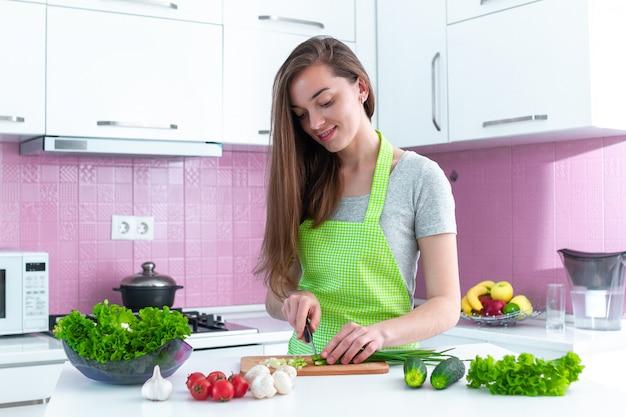 Giovane donna di cucina che taglia le verdure a pezzi per insalate e piatti freschi sani in cucina a casa Foto Premium