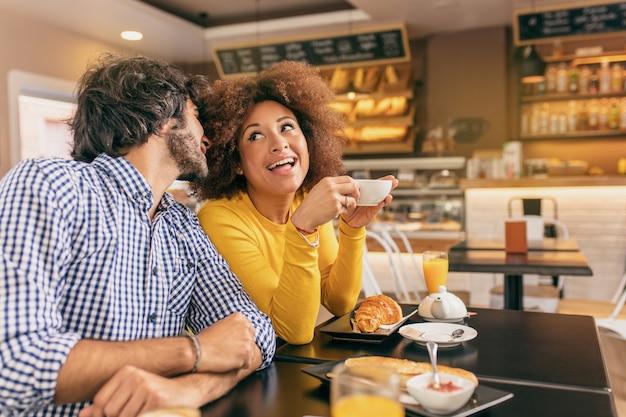 Giovane coppia al caffè, il ragazzo le sta bisbigliando e lei è sorpresa. Foto Premium