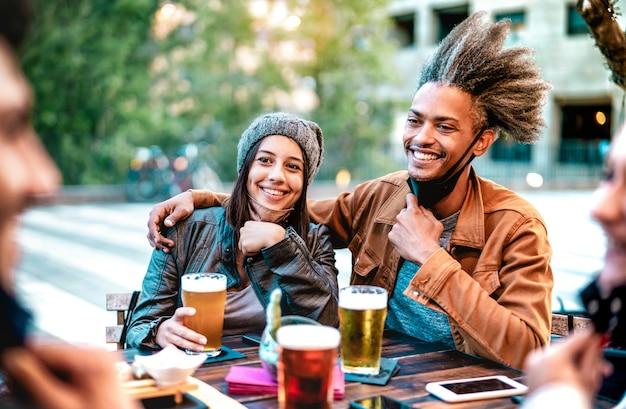 Giovani coppie che bevono bicchieri di birra che indossano maschere facciali aperte con focus sulla donna Foto Premium