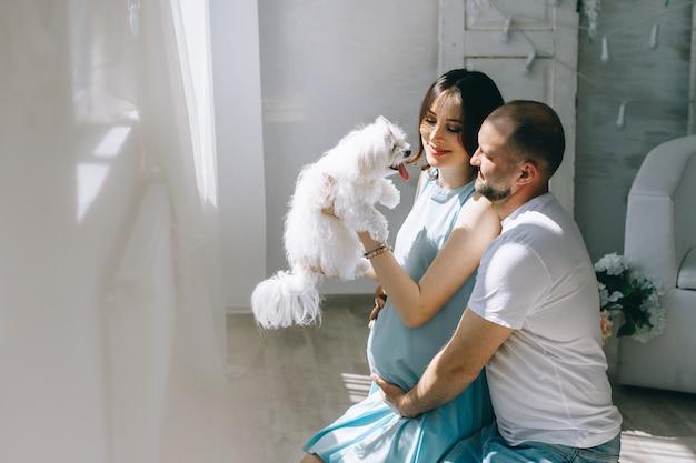 Giovani coppie che prevedono bambino in piedi insieme al chiuso Foto Premium