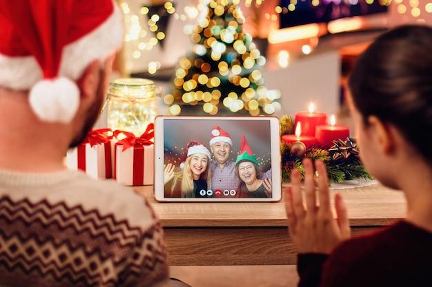 Giovani coppie che hanno una videochiamata di natale con la loro famiglia. concetto di famiglia in quarantena a natale a causa del coronavirus Foto Premium