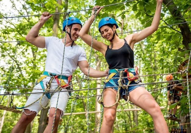 Giovani coppie che hanno tempo di divertimento nel parco avventura avventura Foto Premium
